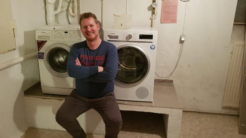 Zufriedener Handwerker auf fertigen Podest für Trockener und Waschmaschine